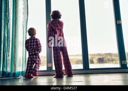 Boys in pajamas looking out window - Stock Photo