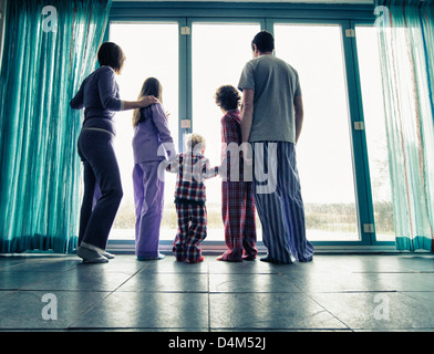 Family in pajamas looking out window - Stock Photo