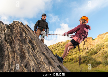People abseiling in rock climbing lesson - Stock Photo