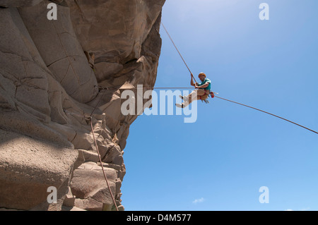 Rock climber abseiling jagged cliff - Stock Photo