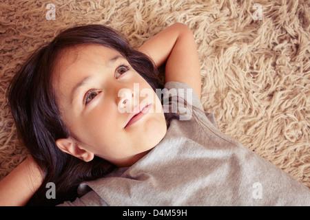 Girl laying on shag carpet - Stock Photo