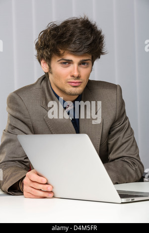 Portrait of handsome young business man looking at the camera and smiling confidently while working at his laptop. - Stock Photo
