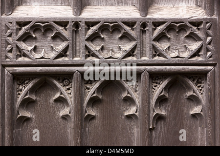 Detail of old Gothic carved oak wood church door, St Martin's Church, Stamford, Lincolnshire, England, UK - Stock Photo