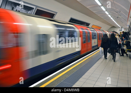 London Underground Central Line tube train departing train station people on platform with motion blur Shepherds - Stock Photo