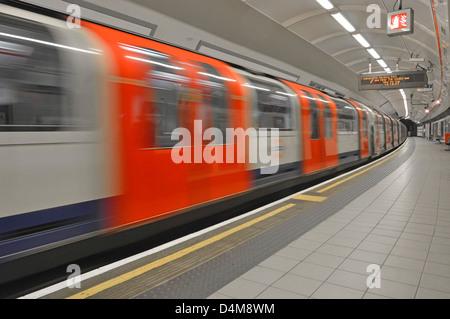 Empty platform on London Underground station with motion blur Central Line tube train departing  Shepherds Bush - Stock Photo
