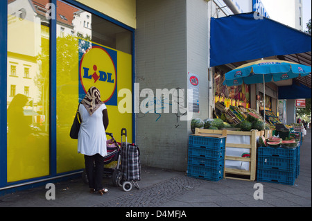 Berlin, Germany, a Muslim woman with a baby carriage in front of a supermarket - Stock Photo