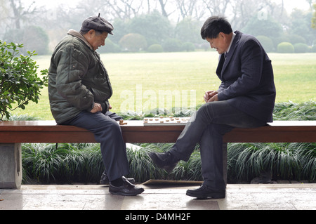 Two men playing Chinese chess at West Lake, Hangzhou, China - Stock Photo