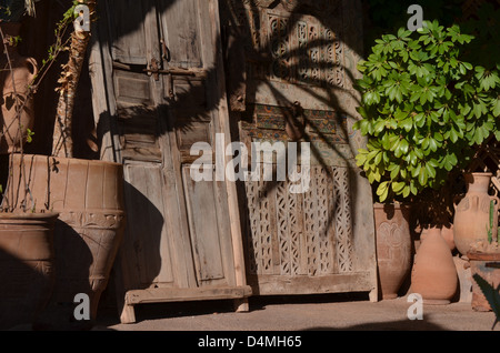 Moroccan carved wooden panels terracotta plant pots with Palm shadow - Stock Photo