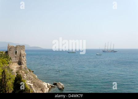 Greece. Samos. Boats ships sailing the Aegean Sea near the ruins of the old Byzantine castle in the town of Pythagoreio. - Stock Photo