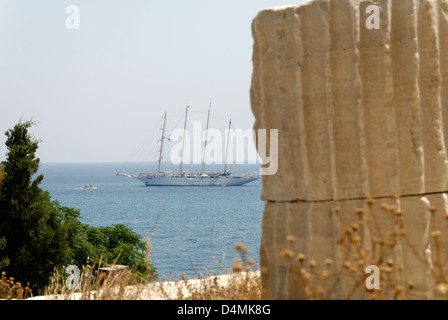 Greece. Samos. View of a ship sailing near ruins of the old Byzantine castle Kastro in the town of Pythagoreio. - Stock Photo