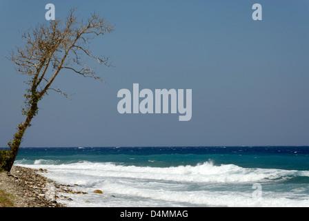 Samos. Greece. Waves of the Aegean Sea splash into the pebbly shoreline near the northern coastal town of Agios - Stock Photo