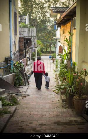 March 12, 2013 - Luang Prabang, Laos - A man and his son walk down a small street in Luang Prabang, Laos. Luang - Stock Photo