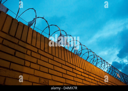 A yellow brick fence with barbed wire on top of it - Stock Photo
