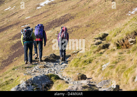 Three tired hikers walking up towards the Hole in The Wall by Helvellyn in the Lake District - Stock Photo
