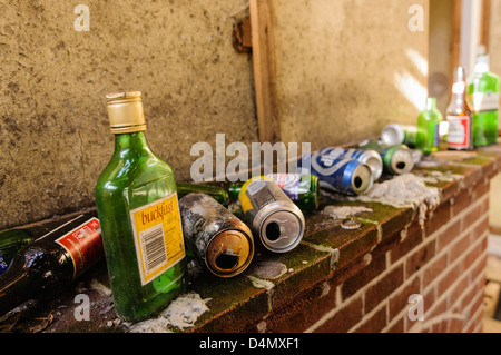 Lots of alcohol bottles and tins on the hearth of a very dirty house. - Stock Photo