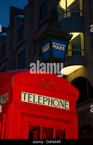 Red telephone box outside police station, Soho, London, England - Stock Photo