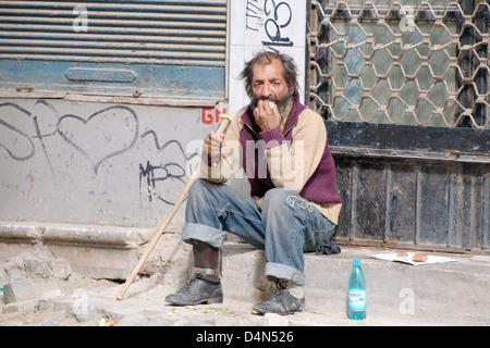An elderly homeless man eating on the street, Bucharest, Romania, Europe - Stock Photo