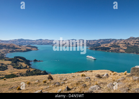 View of Akaroa Harbour, near Christchurch, New Zealand, with the Cunard cruise liner Queen Mary 2 at anchor in deep - Stock Photo