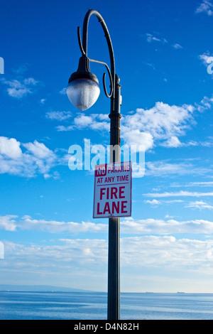 Light pole on Santa Monica Pier holds a No Parking sign. - Stock Photo
