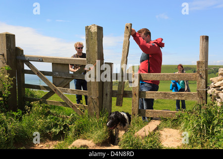 Young people walking on south west coast path with a Springer Spaniel dog using dog-friendly access stile in Purbeck - Stock Photo