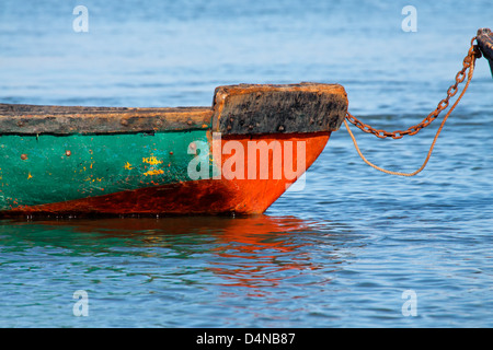 Anchored wooden fishing boat with reflection in water - Stock Photo