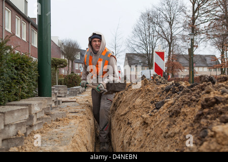 Hungarian migrant worker digging for the construction of a glass fiber network in the Netherlands - Stock Photo