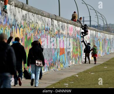 Demonstrators climb the East Side Gallery, a piece of art and part of the former Berlin Wall in Berlin, Germany, - Stock Photo