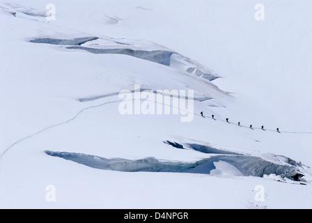 People hiking on Aletsch Glacier near Jungfraujoch, Bernese Alps, Switzerland - Stock Photo