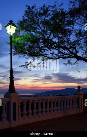 A promenade with a sunset view over Nerja, Spain - Stock Photo