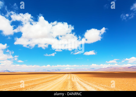 Unpaved road leading straight to a mountains range - Stock Photo