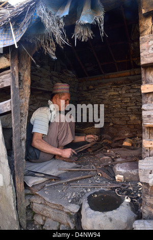 Traditional Nepalese village Blacksmith, at work in his Forge - Stock Photo