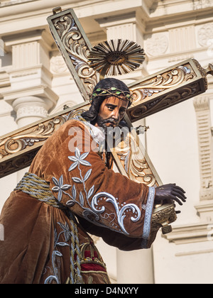 Statue of Jesus Christ in robes bearing a cross - Stock Photo