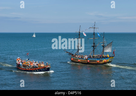 Pleasure boats with tourists in Whitby Bay, North Yorkshire, UK - Stock Photo