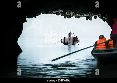 Boats sailing with tourists in Halong Bay in Vietnam. One boat in foreground another in background. Scenic view - Stock Photo
