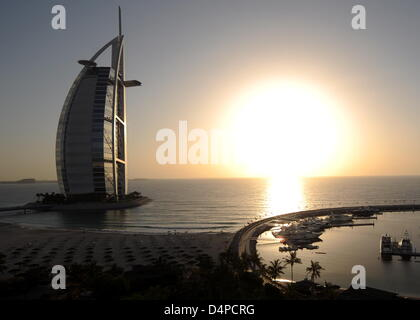 The sun sets behind the Burj al Arab Hotel in Dubai, United Arab Emirates, 31 May 2009. The luxury hotel is one - Stock Photo