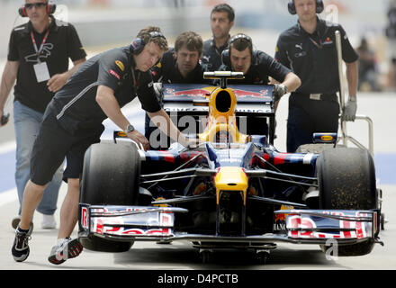 The race car of German Formula One driver Sebastian Vettel of Red Bull Racing is pushed back into the pits during - Stock Photo