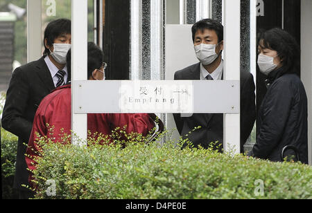 People stand outside the Japanese International School after a swine flu test in Duesseldorf, Germany, 11 June 2009. - Stock Photo