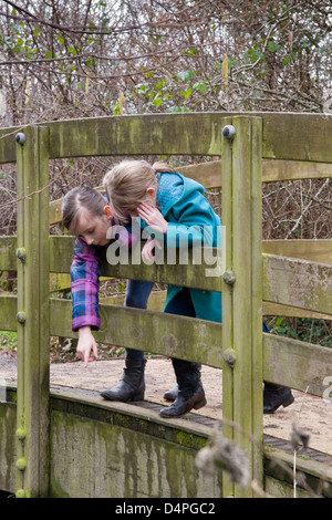Two young Caucasian girls leaning over foot bridge and pointing at something, taken in Bristol, UK - Stock Photo