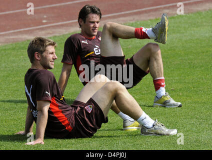 Players Thomas Hitzlsperger (L) and Christian Traesch of German Bundesliga club VfB Stuttgart stretch after the - Stock Photo