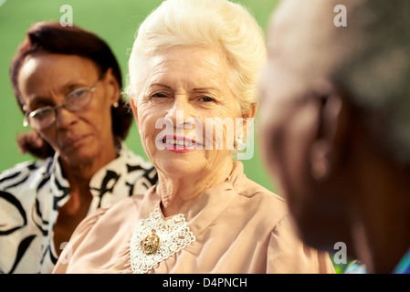 three old women sitting on bench in park and talking - Stock Photo