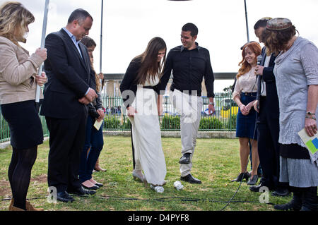 Bride Lin Dror and groom Alon Marcus break two glasses concluding their Reform wedding ceremony in a tradition reserved - Stock Photo