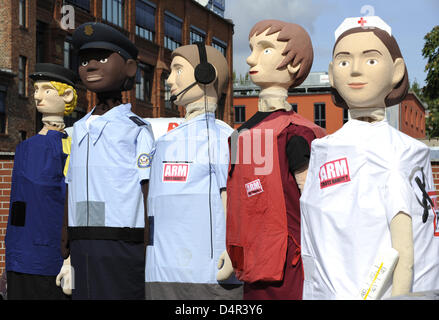 Oversized figures of a postman, a security officer, a telephone operator, a hairdresser and a nurse are pictured - Stock Photo