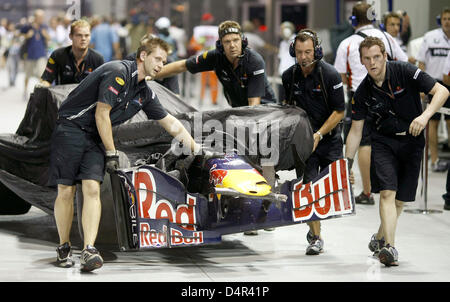 Mechanics push the crashed car of Australian Formula One driver Mark Webber of Red Bull Racing back to the pits - Stock Photo