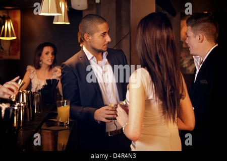Young businessman hanging out and talking with friends at the bar - Stock Photo