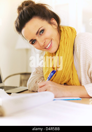 Closeup of a cheerful woman writing something in her journal - Stock Photo