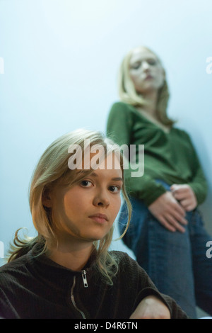 Teenage girl looking at camera, friend in background - Stock Photo