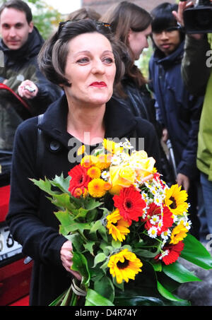 Nobel Prize laureate Hertha Mueller (L) leaves her apartment with a bunch of flowers in Berlin, Germany, 08 October - Stock Photo