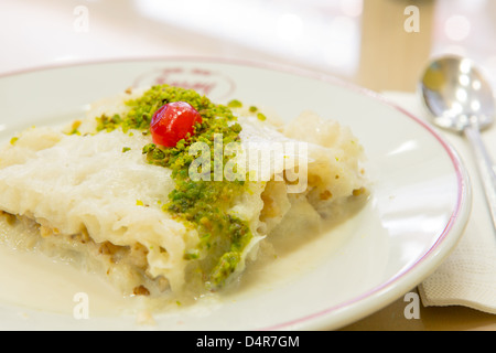 Traditional Turkish Ramadan dessert Gullac made with Phyllo Dough and sweetened milk, served with pistachio crumble - Stock Photo