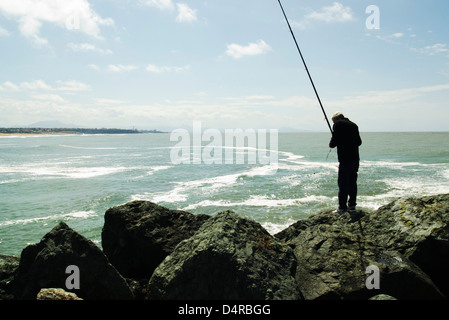 Fisherman and his fishing rod, port of Biarritz on the horizon - Stock Photo