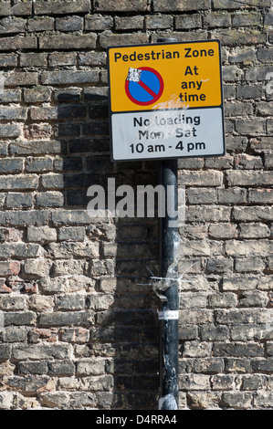A pedestrian zone and no loading sign on a post against a brick wall at St Andrew's Street Cambridge UK - Stock Photo